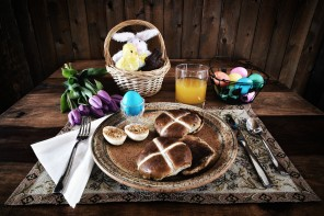 A place setting of Easter Breakfast of eggs and hot cross buns.  Processed in a lightly bleached rustic retro style.